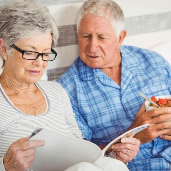 senior-couple-reading-magazine-in-bedroom