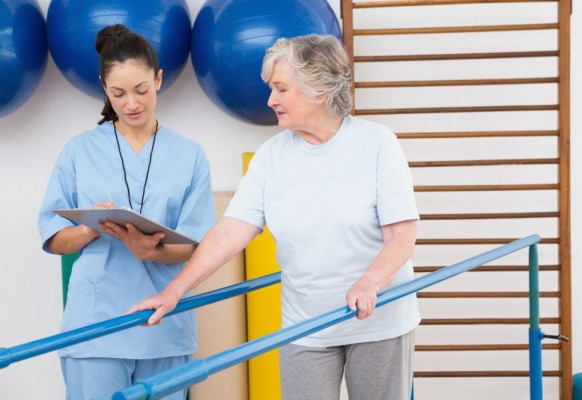 senior-woman-walking-with-parallel-bars-with-therapist